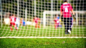 Group of little boys playing soccer on grass soccer field. Shot from behind one of the goals. Kids are out of focus.